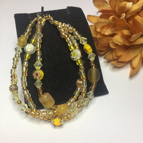 Triple string shades of lemon beads bracelet