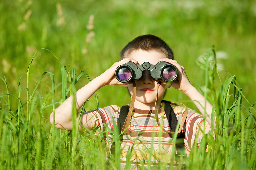 A young boy with binoculars crouching in grass looking back