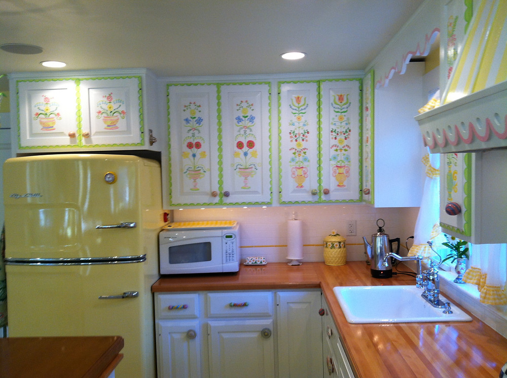 Fun handprinted cabinets with the happy yellow fridge