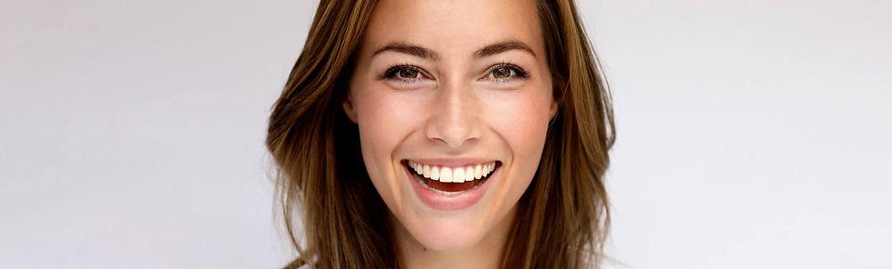 nærbilde av ung kvinne med et stort smil og usynlig tannregulering bak tennene foto