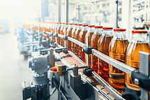 Conveyor belt, juice in glass bottles on