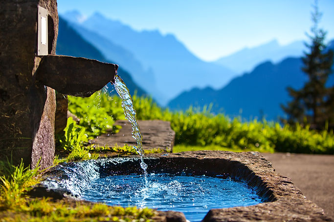 Water spring on Alps mountains backgroun