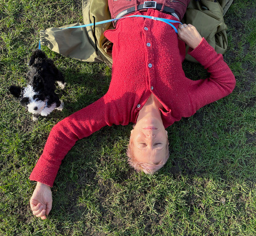 smiling woman lying on lawn with a puppy