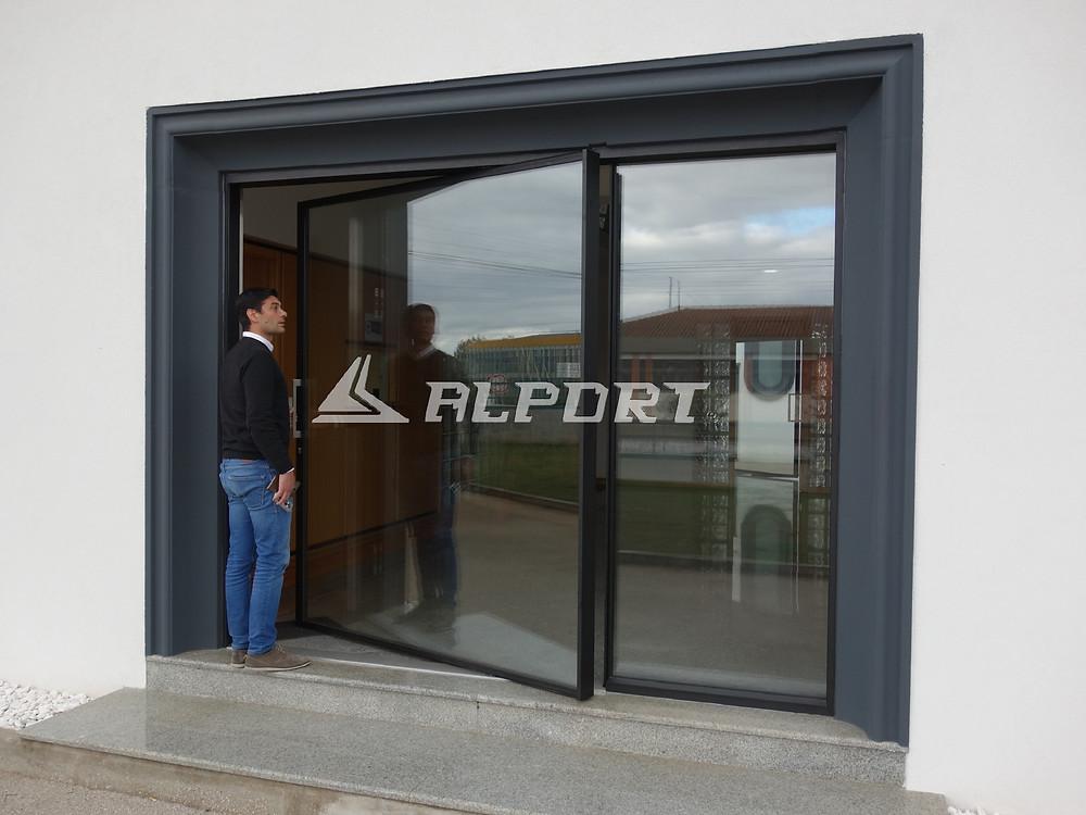 Περιστρεφόμενη πόρτα αλουμινίου κατά τον κάθετο αξονά  της (pivot) σε μεγάλες διαστάσεις με ενεργειακά κρύσταλλα και  κλειδαριά ασφαλείας μηχανική ή ηλεκτρομαγνητική. Μinimal περιμετρικά προφίλ  αλουμινίου λεπτης όψης με την μεγαλύτερη διαφάνεια.