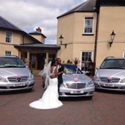 Bride and Groom with wedding cars.