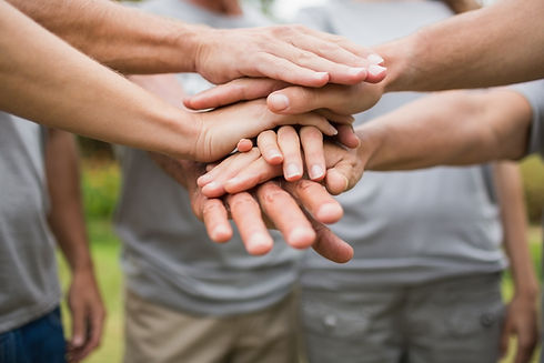 A picture of five peoples hands on top of each other, showing teamwork