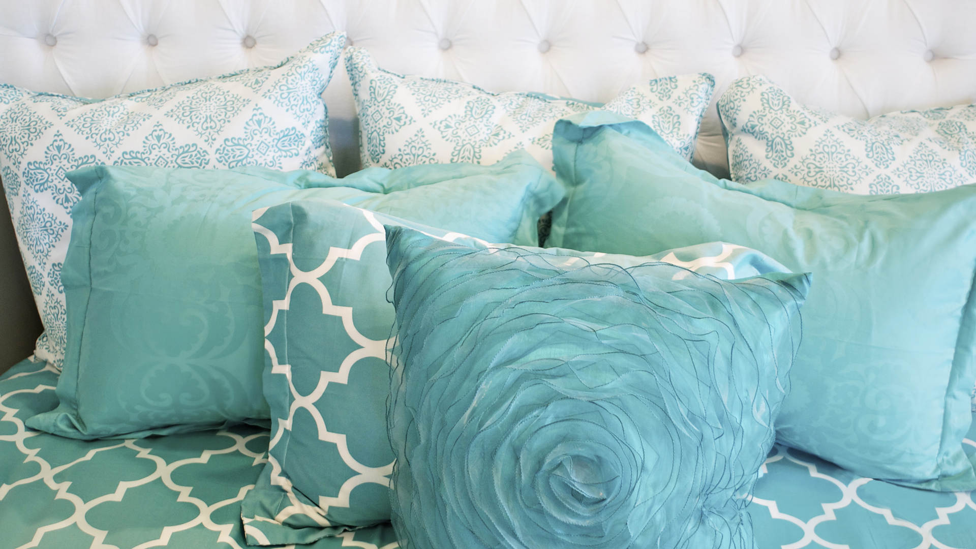 Closeup photo of teal cushions on bed.jp