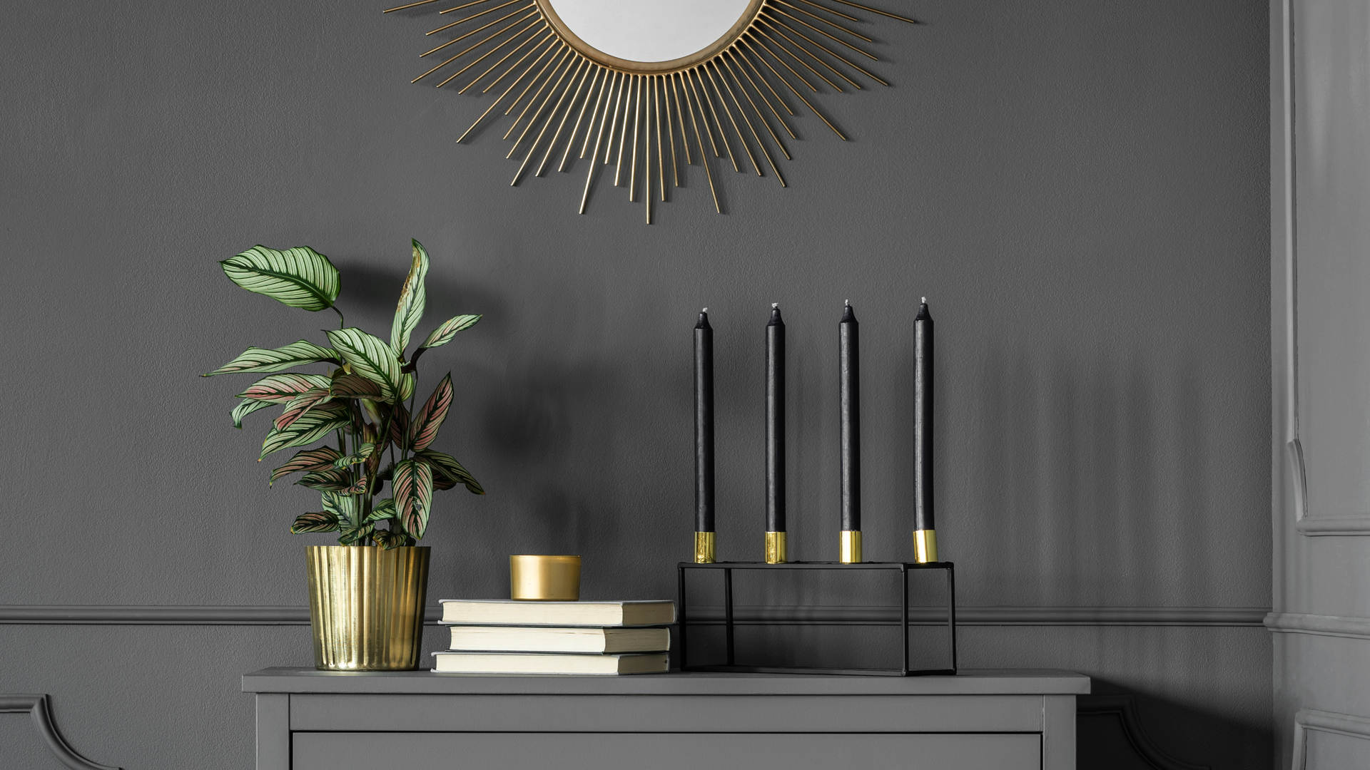 Gold round mirror above grey cabinet wit