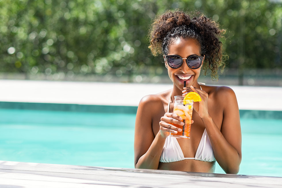 Portrait of happy fashion woman with sunglasses standing in swimming pool drinking cocktai