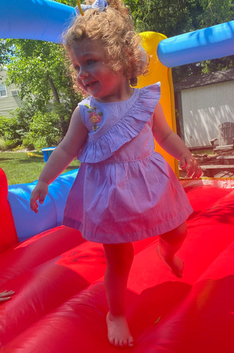 This little sweetheart is jumping  high in a Blu and Blue crossover ruffle striped dress.