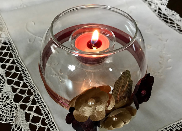 Round glass candle holder with silk flower accents
