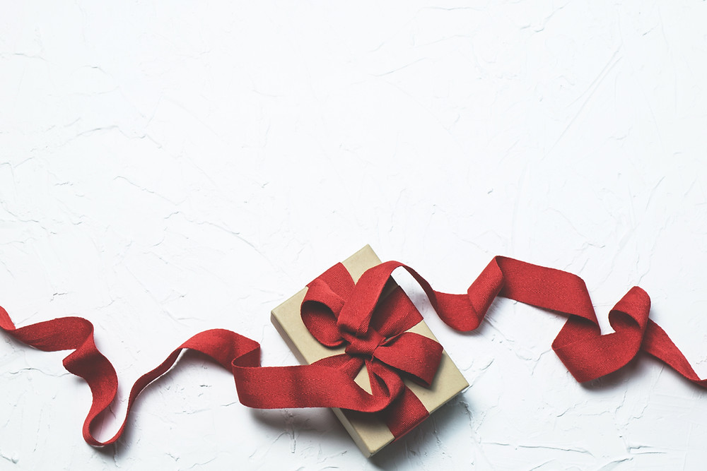 stock photo of a small gift box with a long red ribbon