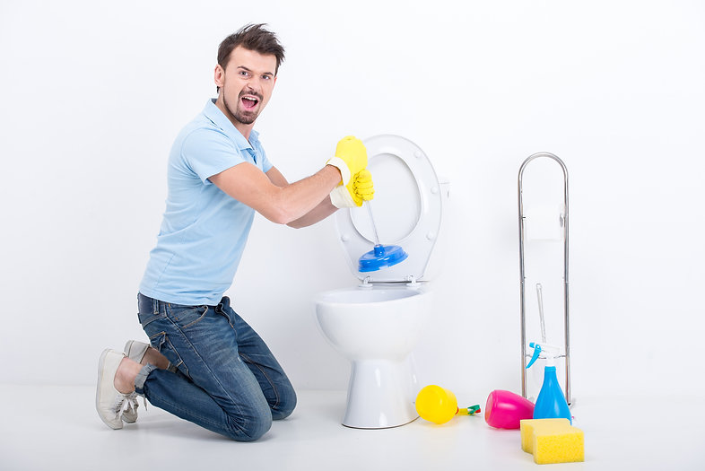 Young man unclogging a toilet with plung