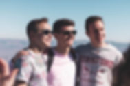 Three male college students with arms around each other staring off camara with a vast landscape in the background.