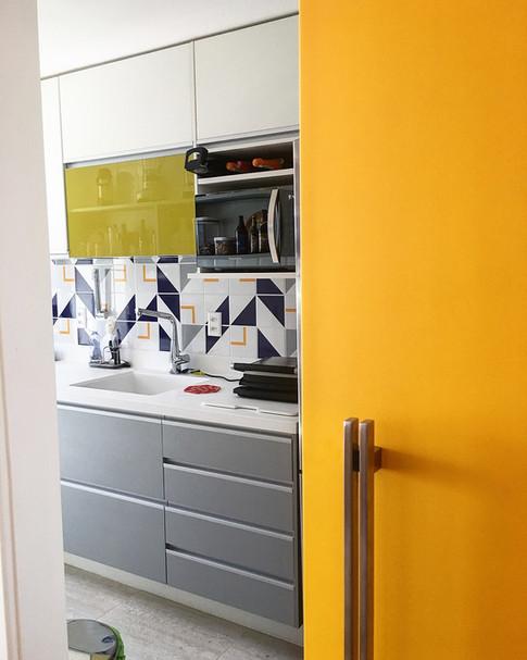 Porta de correr em laca amarela divide sala e cozinha.