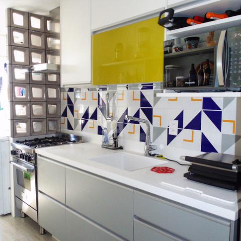 Cozinha em tons de branco e cinza colorida por azul e amarelo.
