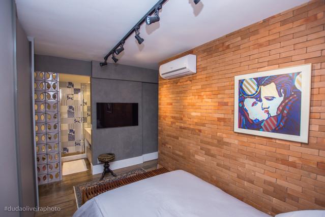 Quarto do casal integrado com banheiro, onde uma parede em cobogós cinza serve de tapa-vista.
