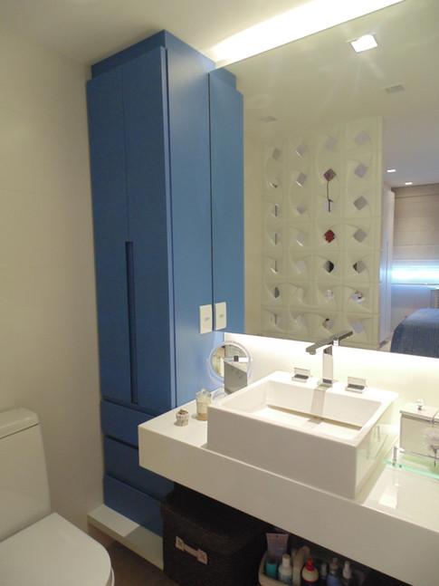 Banheiro todo branquinho com armario vertical em azul.