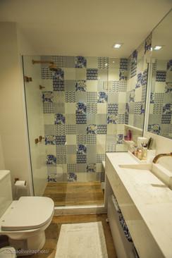 Banheiro da suíte com mosaico azul, branco e dourado e metais Red Gold.