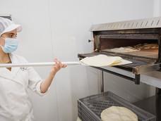 Hanna precociendo las bases de las pizzas