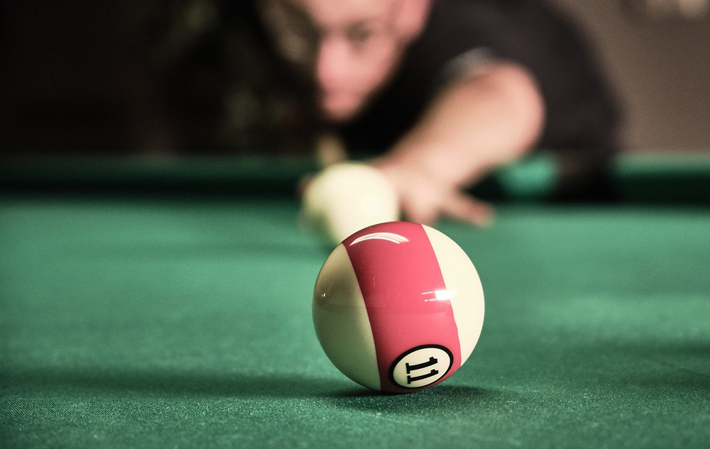 A pool player lines up the white ball with intense focus as he aims at the target ball.