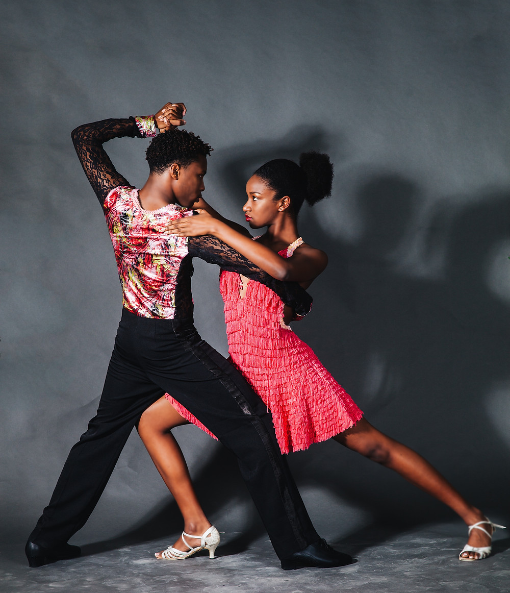 A couple - man and woman - hold a dramatic dance pose illustrating the nature of reciprocal movement when two people are dancing with each other.