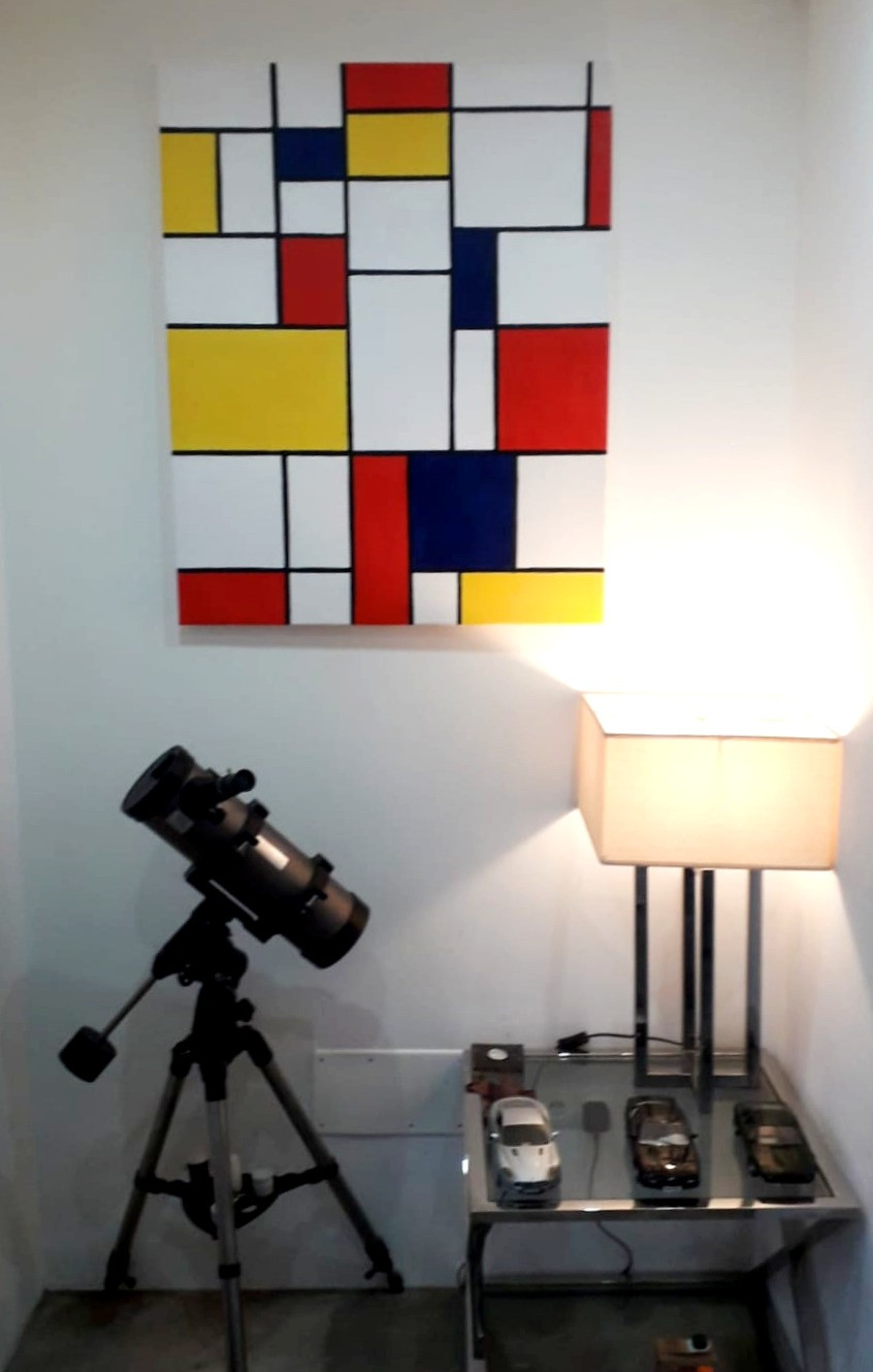 A painting inspired by Piet Mondrian's grid paintings in black, white, red, yellow and blue, seen hanging on the wall in the client's home.