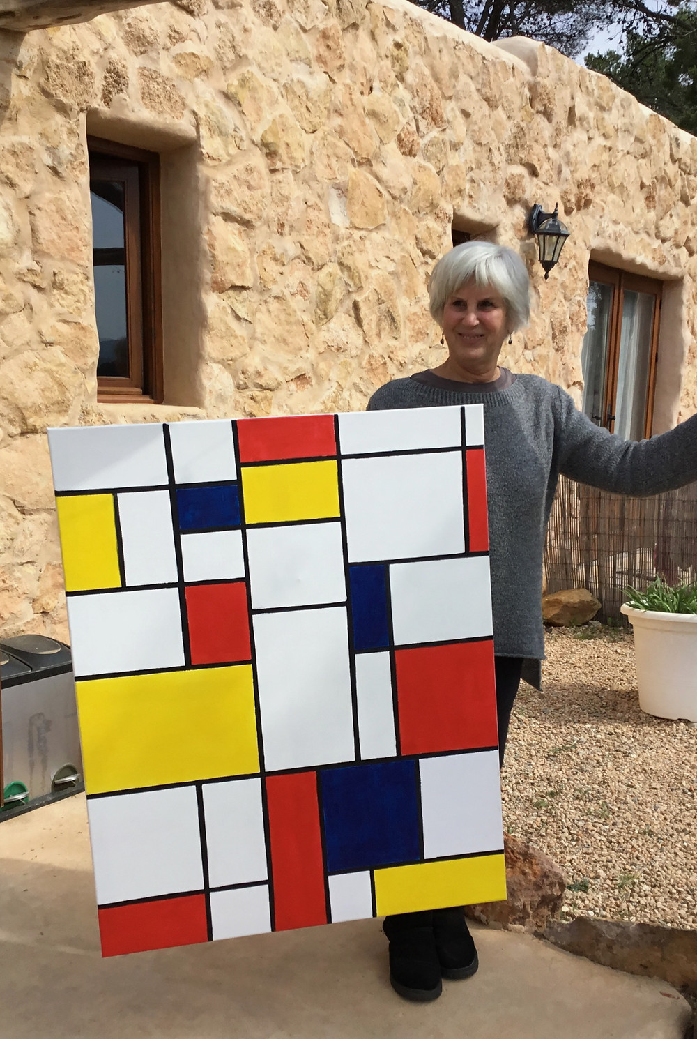The artist displays the finished Mondrian-inspired grid painting in black, white, red, yellow and blue.