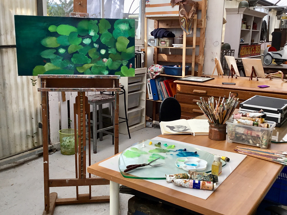 An artist's studio showing green painting on an easel, a palette of oil paints, artist's brushes, a plan chest.