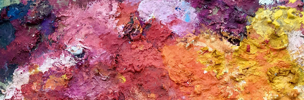 The heavy textures of dried oil paints on an artist's palette. Hues of red, yellow, orange, purple, magenta, blue.