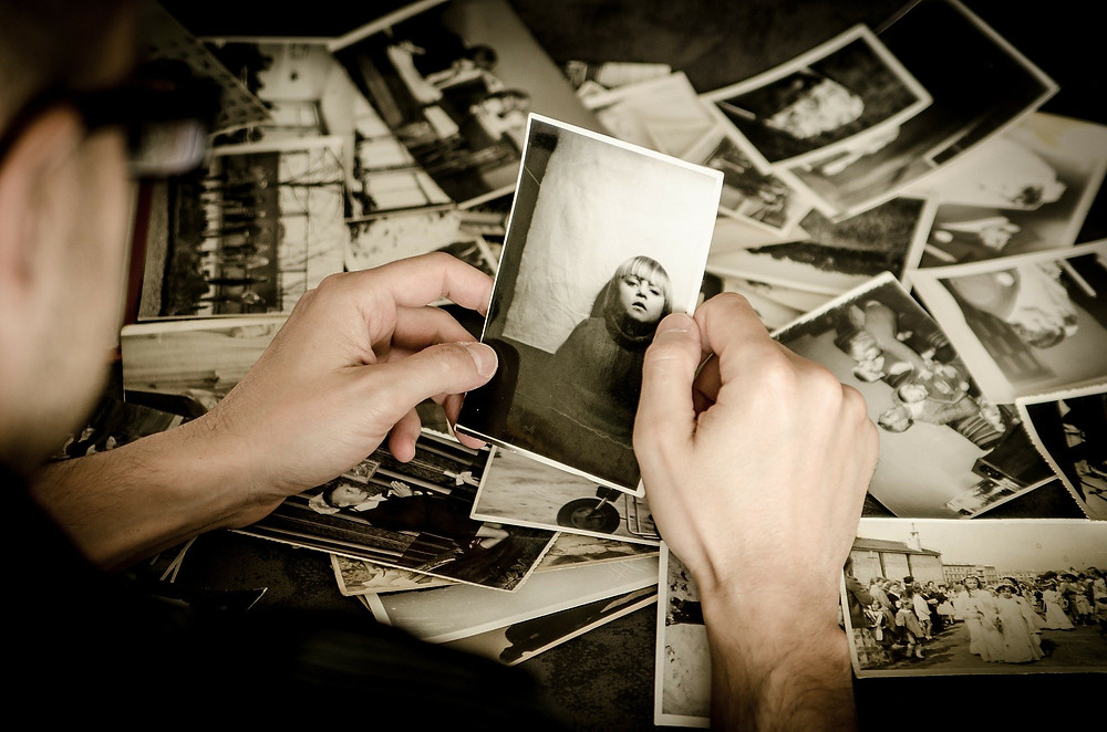A person wearing glasses holds an old black and white photograph of a young blond girl in both hands. On the table behind there are many more old black and white photographs, clearly all taken on an old camera with real film in the days before digital photography.