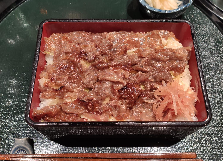 Wagyu Shinshu premium // ventaglio di lamine di wagyu marinate in salsa profumata al sake, scottate e servite su letto di riso bianco e insalata. Servito con zenzero, insalatina di ceci, alghe e daikon marinati