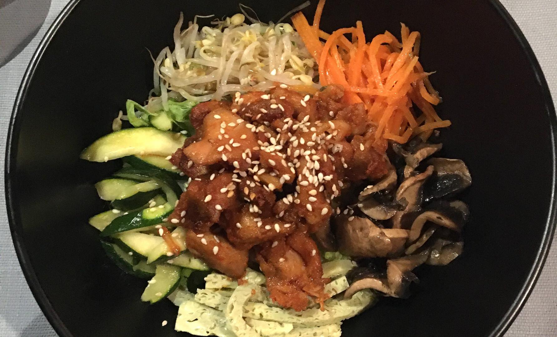 Bibimbab con pollo in salsa Gochujang piccante, germogli di soia, zucchine, carote, funghi, uova, insalata e olio di sesamo