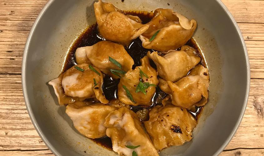 Ravioli fatti a mano con ripieno di maiale, serviti con salsa dolce-piccante