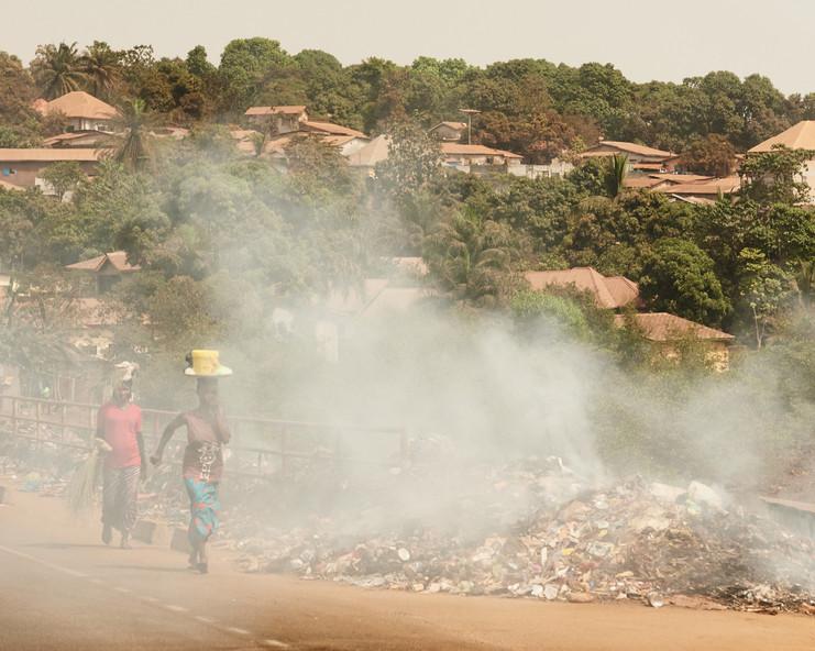 Women running past burning trash, Conakry