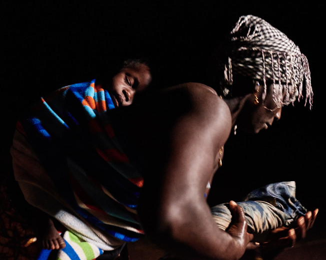 M'bambe Soumah rinsing indigo dyed fabric with her baby