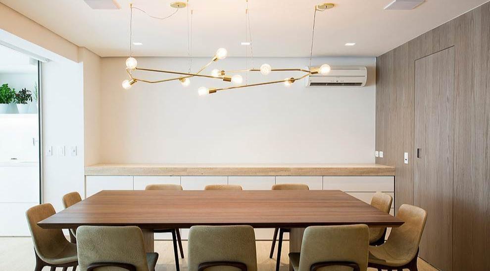 Pendente dourado com várias lâmpadas acima da mesa