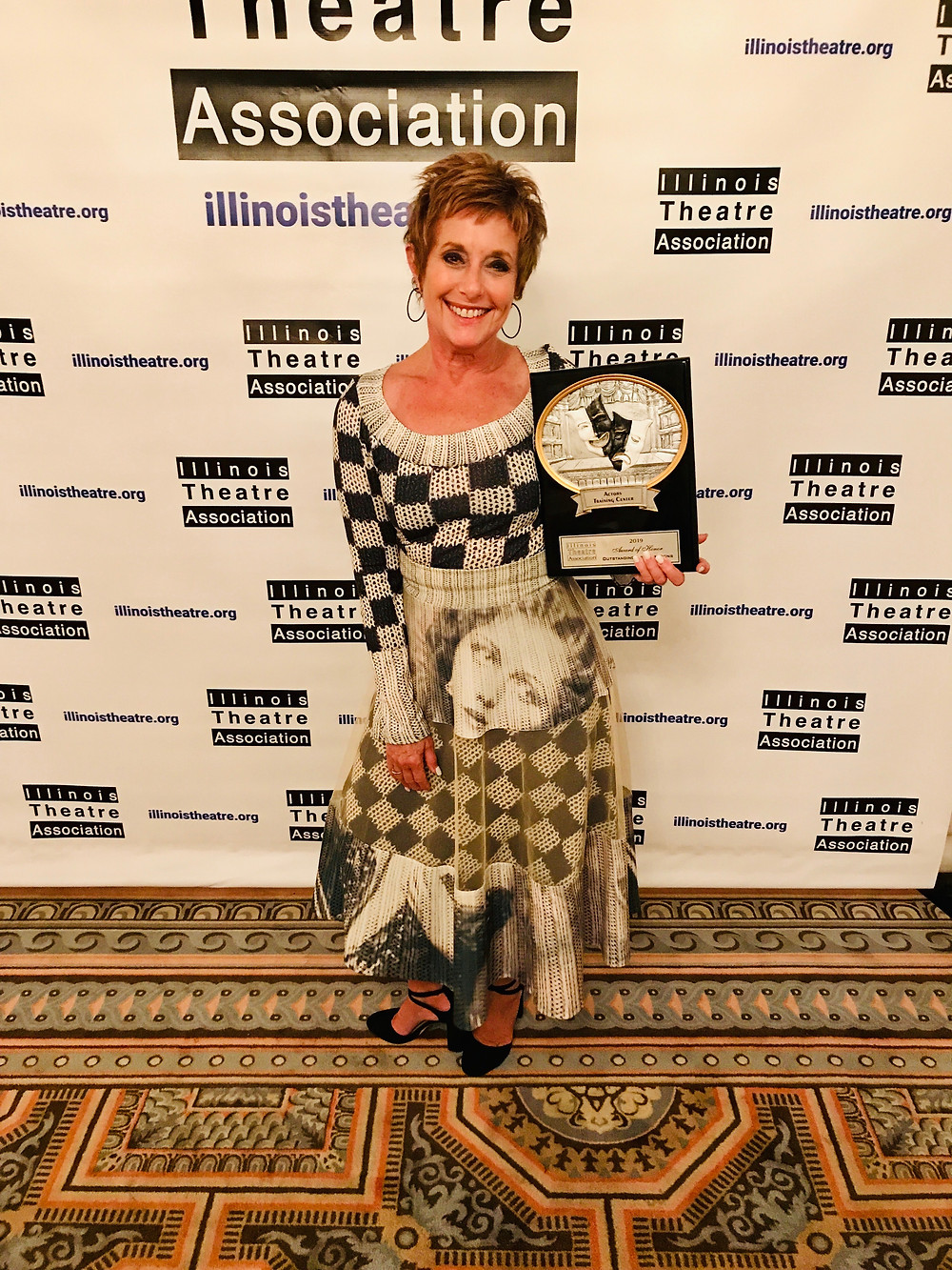 ATC Founder, Carole Dibo, holding the 2019 ITA Award of Honor