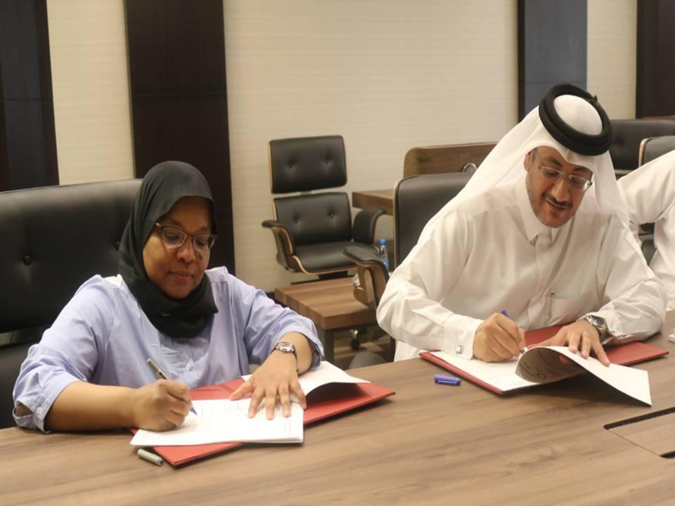 Faleh Al-Naemi and Howaida Nadim Signing Agreement