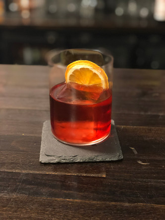 Negroni with clear ice cube and Burnt Orange Garnish