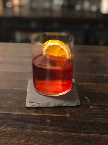 Negroni with clear ice cube and Burnt Orange Garnish