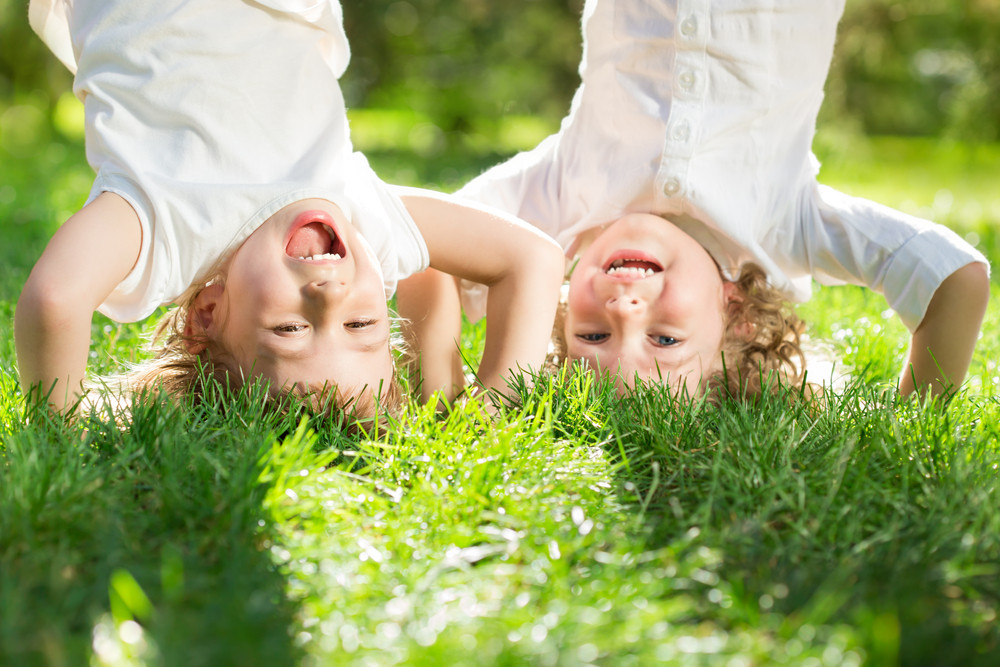 boy and girl doing handstand on green grass