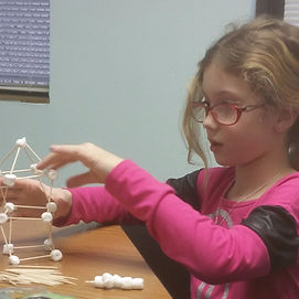 A student building a stucture with marshmallows and toothpicks.