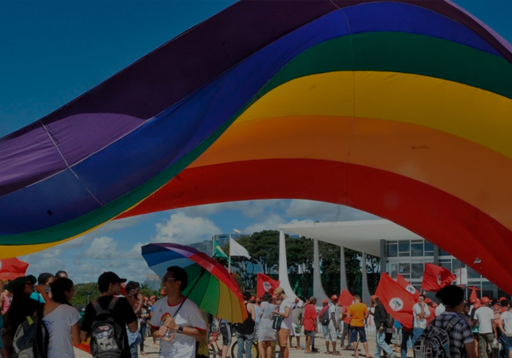 Ativistas LGBTQ+s reunidos em passeata em Brasília, sob bandeira do movimento