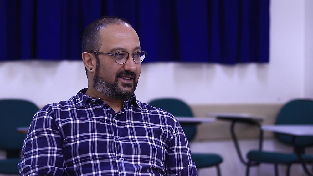 #Enxergandocompalavras: foto do professor Hudson Vilas Boas no dia da entrevista. Ao fundo, cadeiras azuis de uma sala de aula.