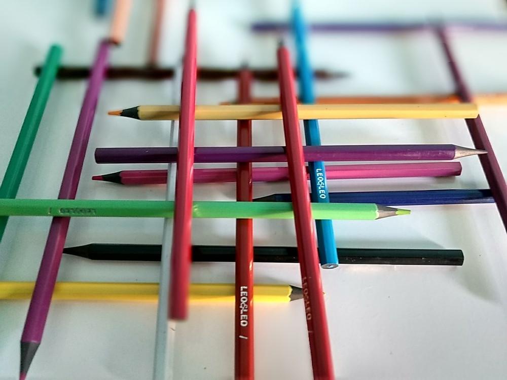 lápis coloridos dispostos de forma paralela e de modo a criar pilhas.