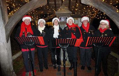 Handbell ringers at the village pump at Christmas
