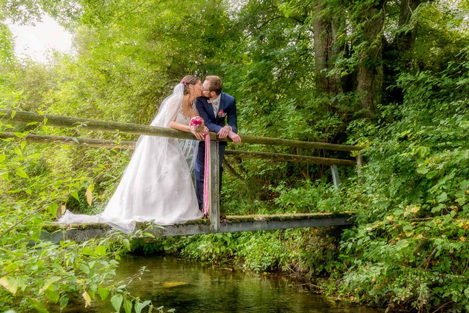 Brautpaar auf der Brücke über dem Bach