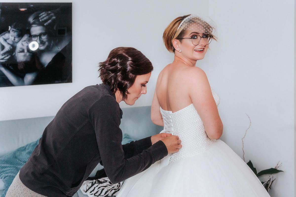 Braut beim Brautkleid Schnüren