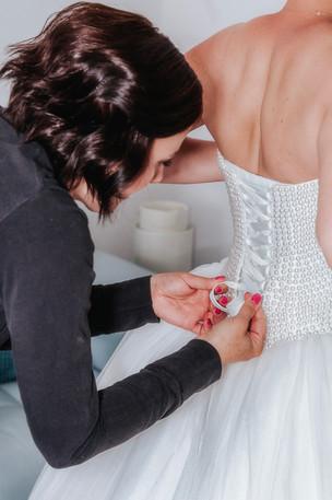 Braut beim Brautkleid Anziehen